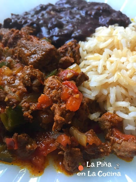 Spicy marinated beef plated with rice and beans close up