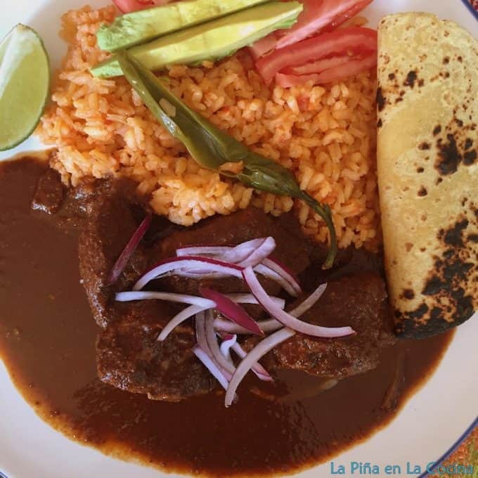 Top view pork in Hibiscus mole sauce with rice, salad and tortilla