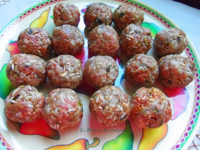 rolled uncooked meatballs on a plate