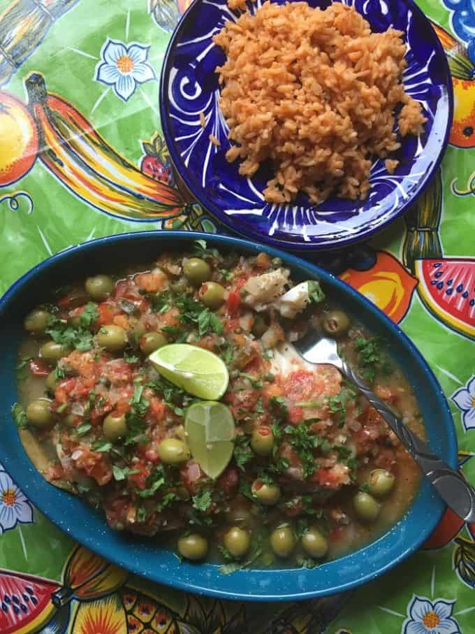 Veracruz style fish plated with salsa on top a side of Mexican rice