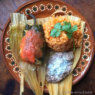 Tamachile garnished with salsa served with rice and beans