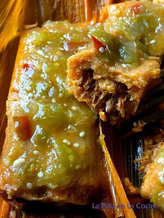 Chile Colorado pork tamales garnished with tomatillo chile de arbol salsa