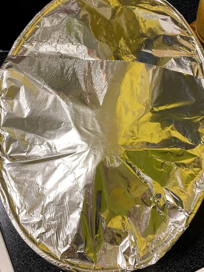Ham in roasting pan covered with foil paper