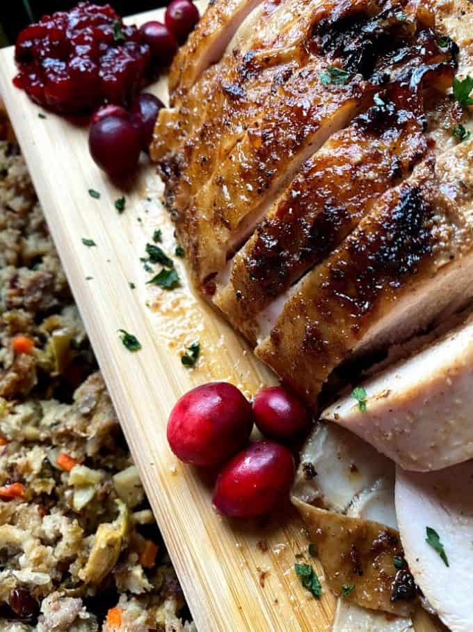 sliced turkey breast on a cutting board with cranberry sauce