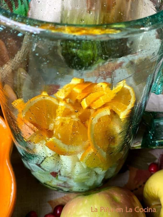 Filling the glass pitcher with diced apples and orange quarters sliced thin
