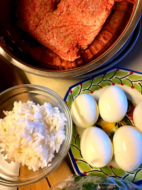 Cooked rice in  a bowl, hard boiled eggs on a plate and uncooked ground beef in a large bowl