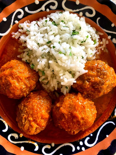 Top view of four meatballs in salsa with white rice in a shallow bowl