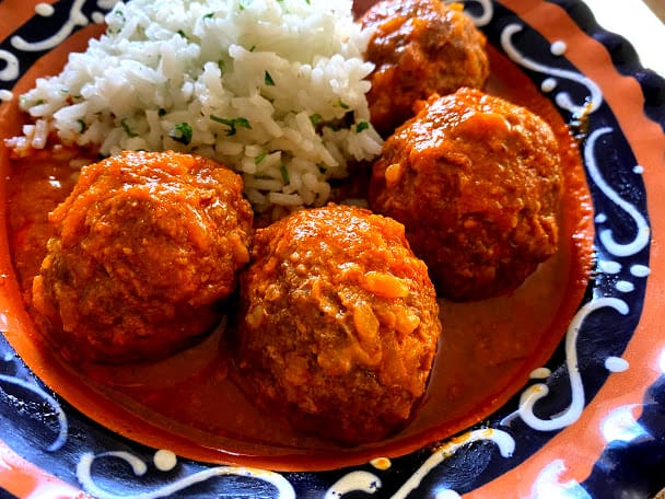 four stuffed meatballs in salsa with white rice in a shallow bowl