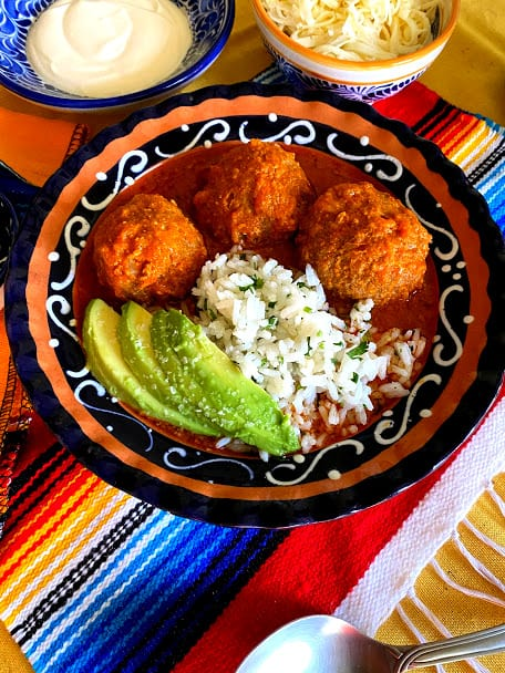 Stuffed Meatballs in salsa, three in a shallow bowl with white rice and avocado slices
