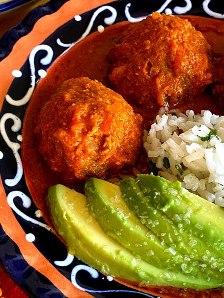 Close up of meatballs in salsa with avocado slices and white rice