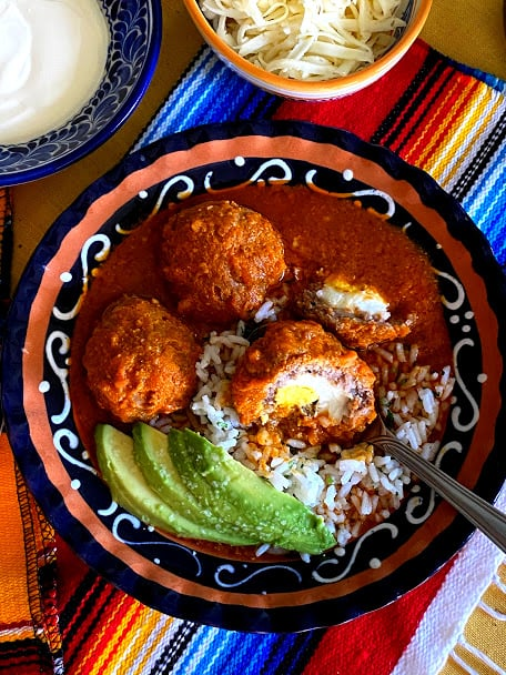 Top view of three meatballs in salsa, one meatball sliced open to show hard boiled egg inside. Served with white rice and avocado slices