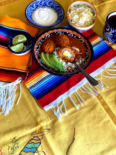 one bowl of albondigas with mexican placemats and tablecloth