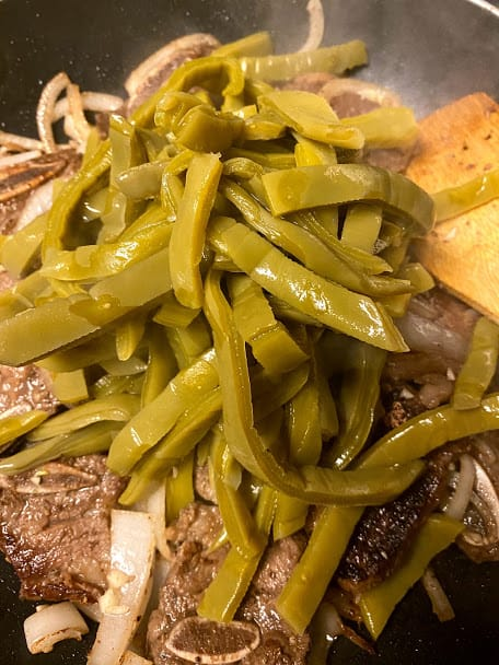 Adding cooked cactus to the beef in saute pan