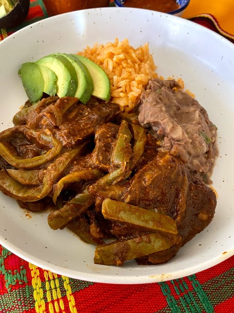 Beef ribs with cactus in a shallow bowl with a side of rice, beans and fresh avocado