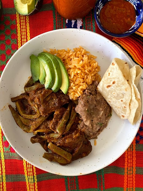 top view of beef ribs with cactus, rice, beans, avocado, tortilla and salsa on the side