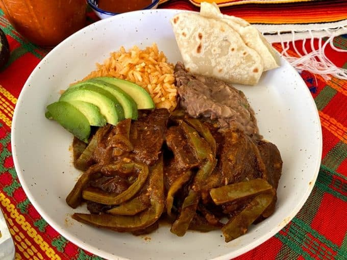 Shallow bowl with beef ribs and cactus, beans, rice, flour tortilla and avocado