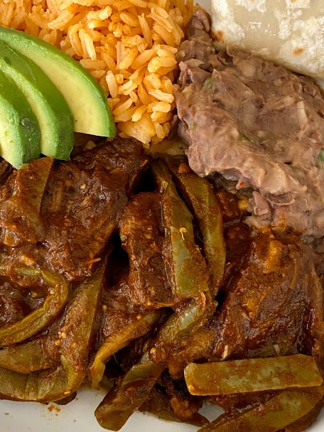 Close up of beef ribs with cactus, rice, beans, avocado and tortilla