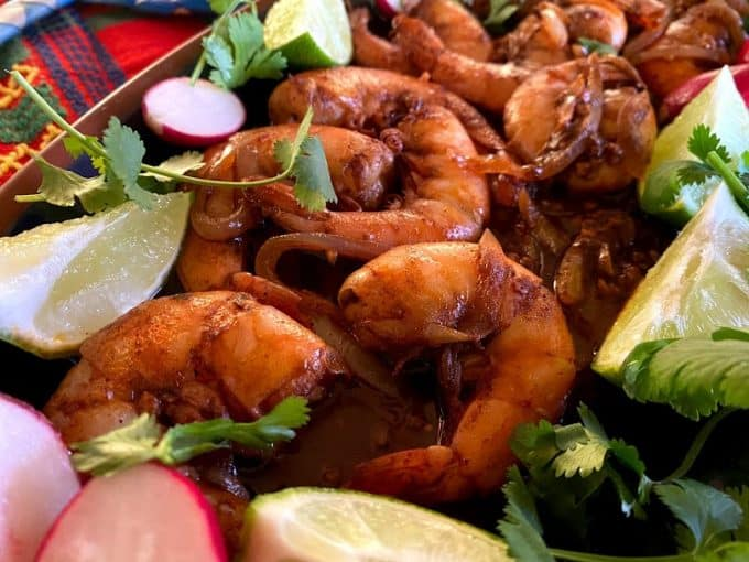 close up of plated spicy shrimp with garnishes of radishes, limes and cilantro