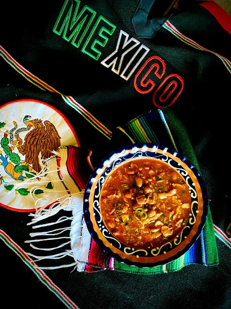 Bowl of drunken beans with Mexican blanket and placemat