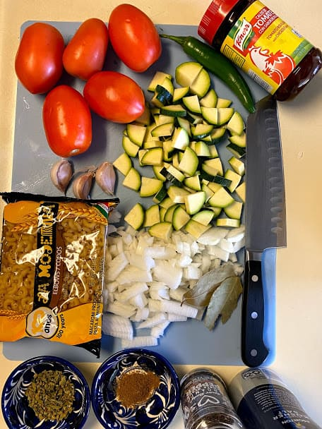 Ingredients for pasta with beef on cutting board with knife
