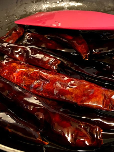 Close up of dried chile puya frying in oil