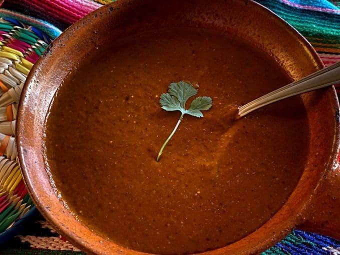 salsa in a Mexican bowl with cilantro garnish, spoon in salsa