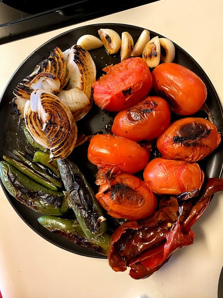 Dry roasted tomatoes, garlic, onion, chile peppers and softened guajillo peppers on a plate