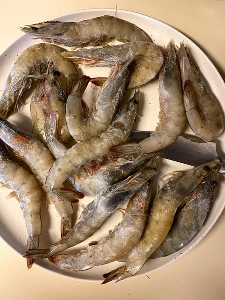 Uncooked shrimp with heads on a big plate