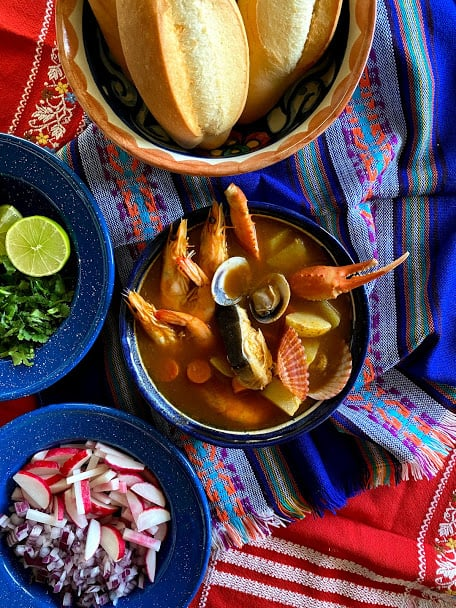 top view of seafood soup with bowls of garnish and bread
