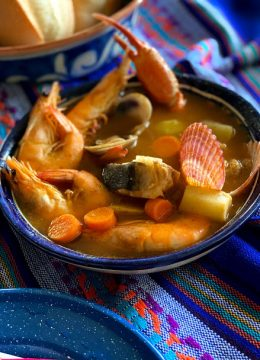 seafood soup in a large deep bowl with bowls of garnish and bread on the table