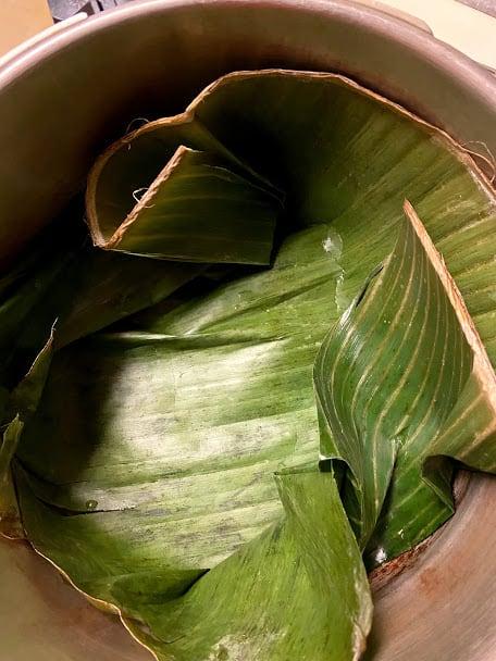 Prepared banana leaves on the bottom of pressure cooker