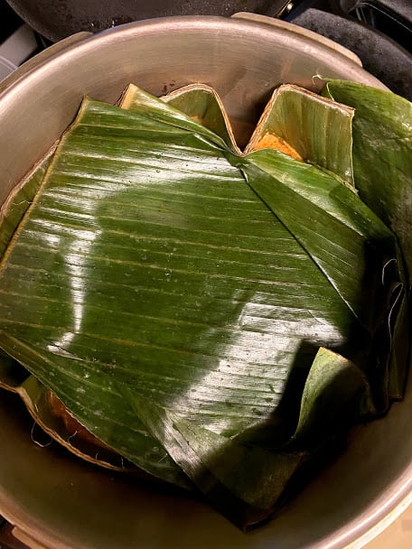 pork covered with prepared banana leaves in pressure cooker