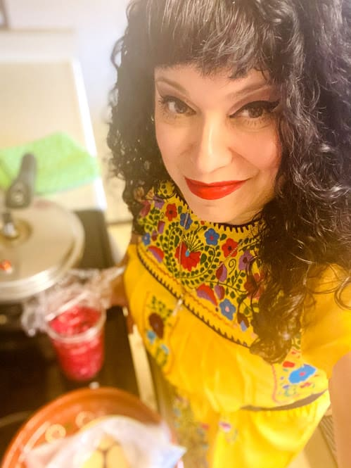 Sonia wearing a yellow embroidered tunic Mexican dress standing in the kitchen
