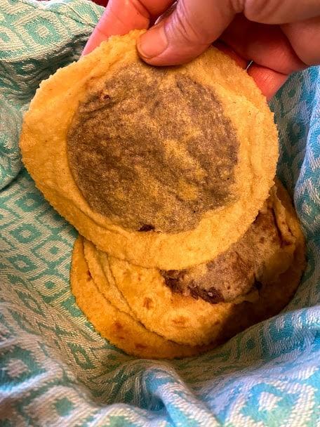 Preparing panuchos, black bean stuffed homemade corn tortillas