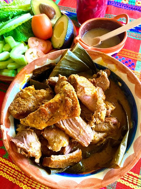 pork pibil in serving bowl close up, habanero salsa and fresh garnishes on the side