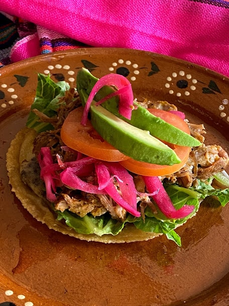 Panucho topped with pork pibil, lettuce, pickled red onions, tomato, avocado and habanero salsa