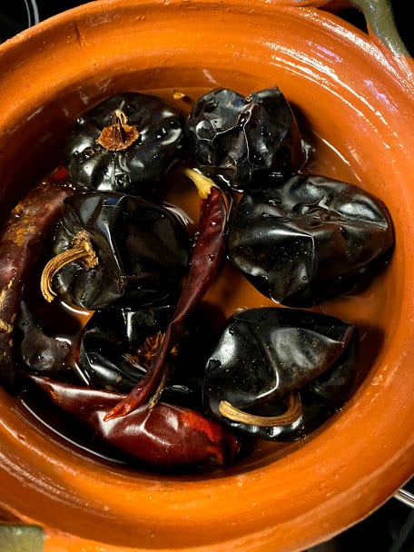 small cazuela with softened chile cascabel and chile puya