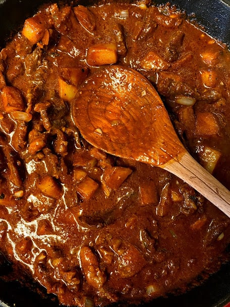 Carne con papa in the skillet with wooden spoon close up