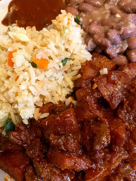 Close up carne con papa with rice and beans plated