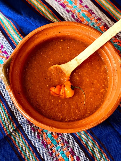 chiltomte salsa in mexican clayware pot with wooden spoon and roasted habanero pepper