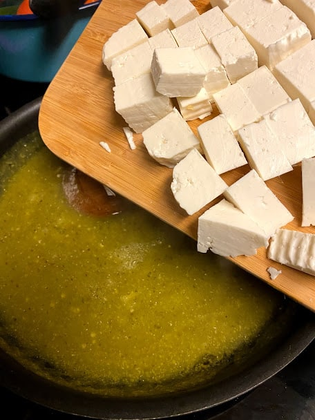 Cubed Mexican panela cheese going into skillet with warm salsa verde