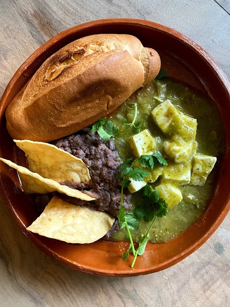 Top view of queso in salsa verde with a side of black beans, toasted bolillo bread and a few tortilla chips