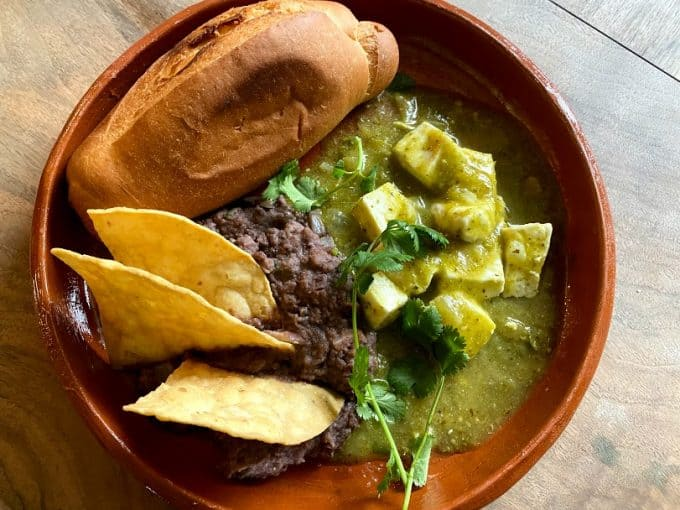 top view of queso in salsa verde plated with black beans, tortilla chips and toasted bolillo bread