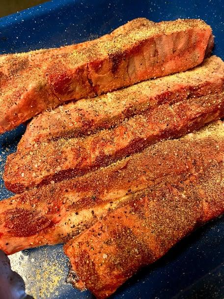 Pork ribs seasoned laying in baking pan