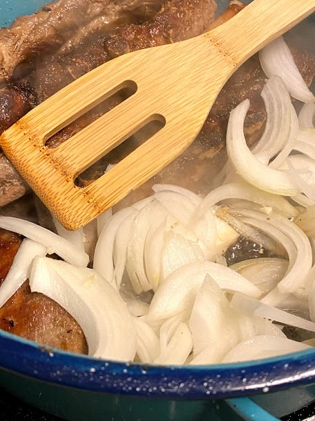 Adding onions to seared pork ribs in pan
