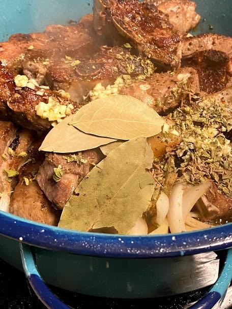 Adding garlic, dried herbs to pork ribs with onions