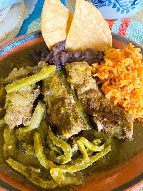 Plated pork ribs with cactus in salsa verde. Served with a side of rice and beans