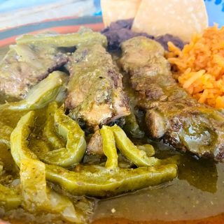 Close up of pork ribs with cactus in salsa verde plated. Rice and black beans on the side of ribs