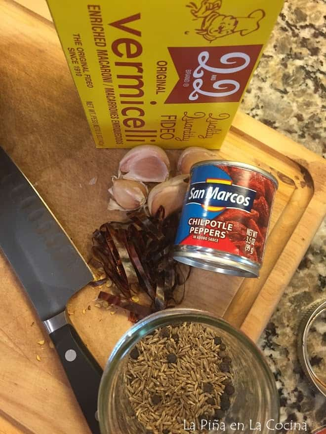 box of fideo, can of chipotles, sliced guajillo and cloves of garlic with knife on cutting board