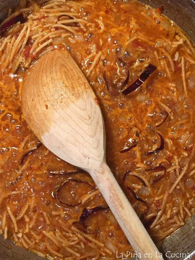 fideo simmering with sauce and broth wooden spoon on top